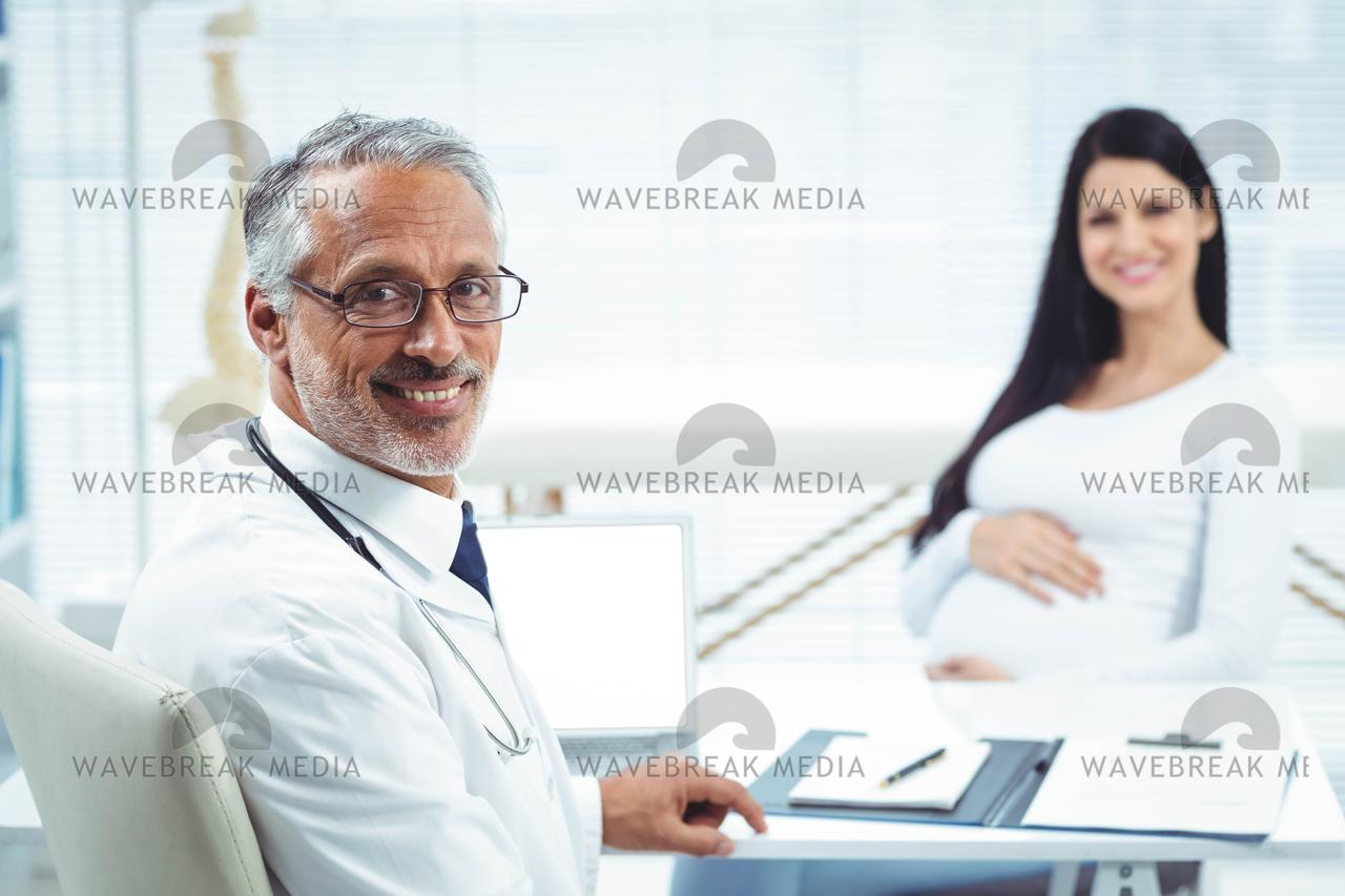 """Pregnant woman sitting at clinic for health checkup"" stock image"