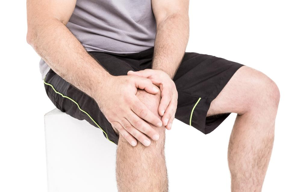 """""""Athlete clutching knee in excruciating pain"""" stock image"""
