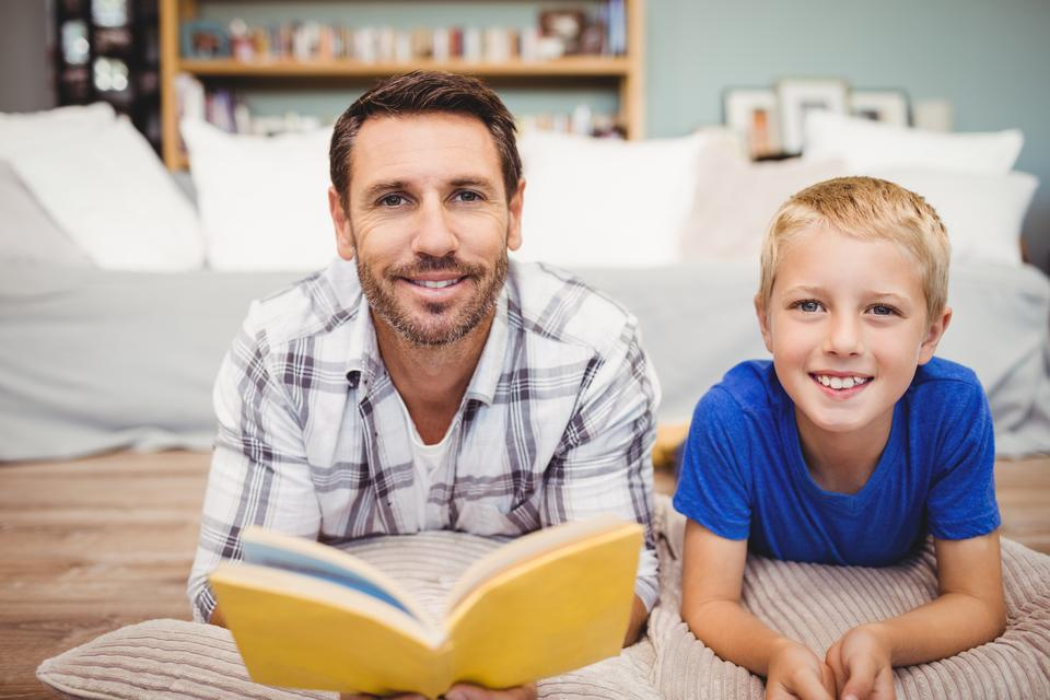 """Father and son holding book lying on floor at home"" stock image"