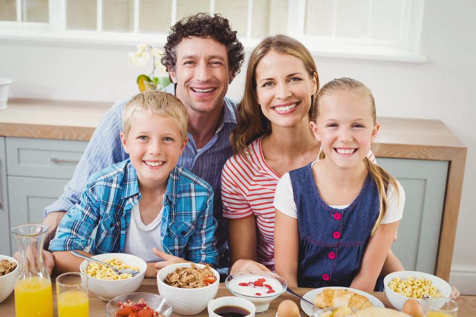 """""""Cheerful children and parents having breakfast by table"""" stock image"""