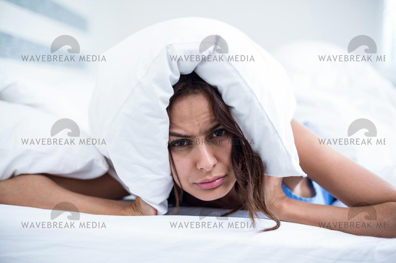 """""""Portrait of irritated woman lying on bed"""" stock image"""