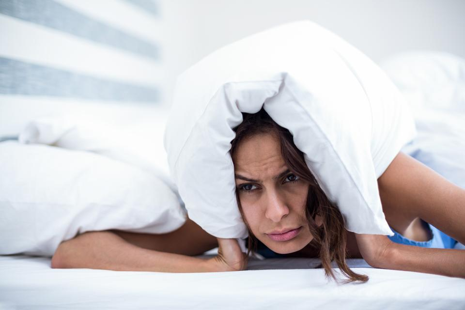 """Irritated woman lying on bed"" stock image"