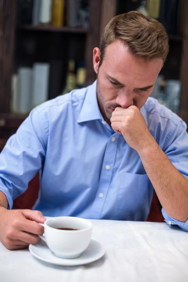 """Depressed man holding coffee cup"" stock image"
