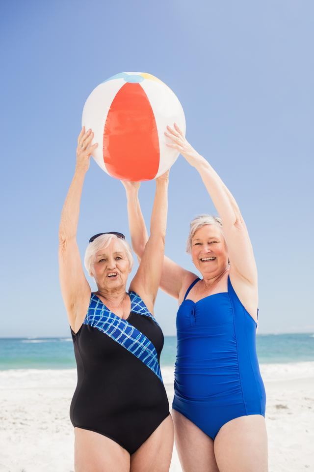 """Senior woman holding beach ball"" stock image"