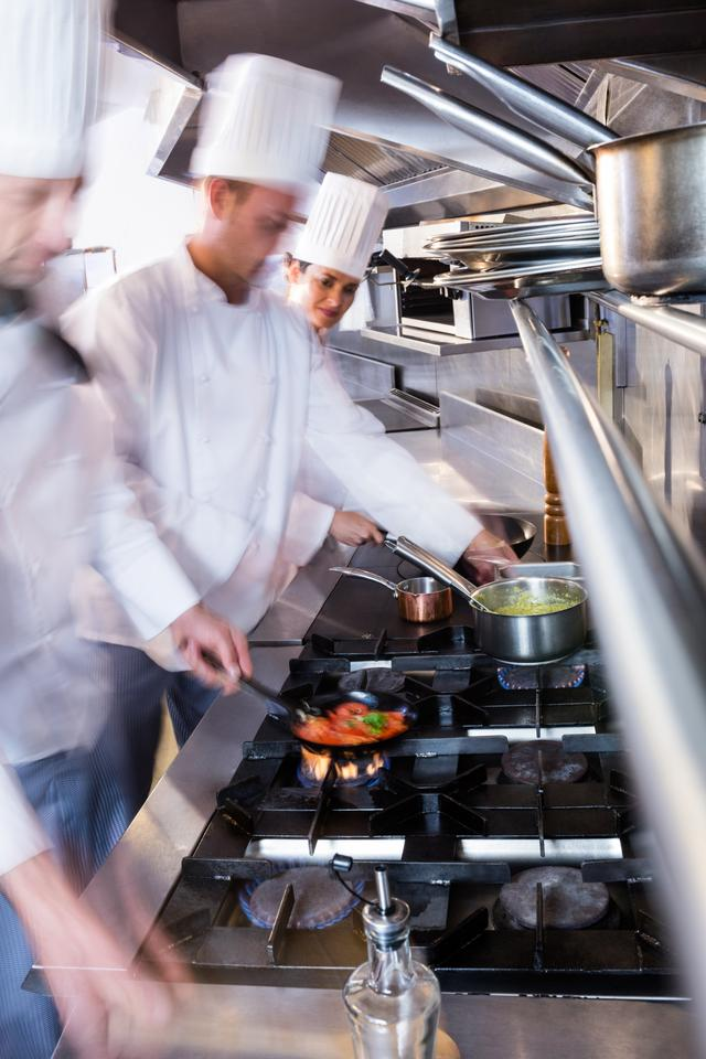 """Chefs preparing food in the kitchen"" stock image"