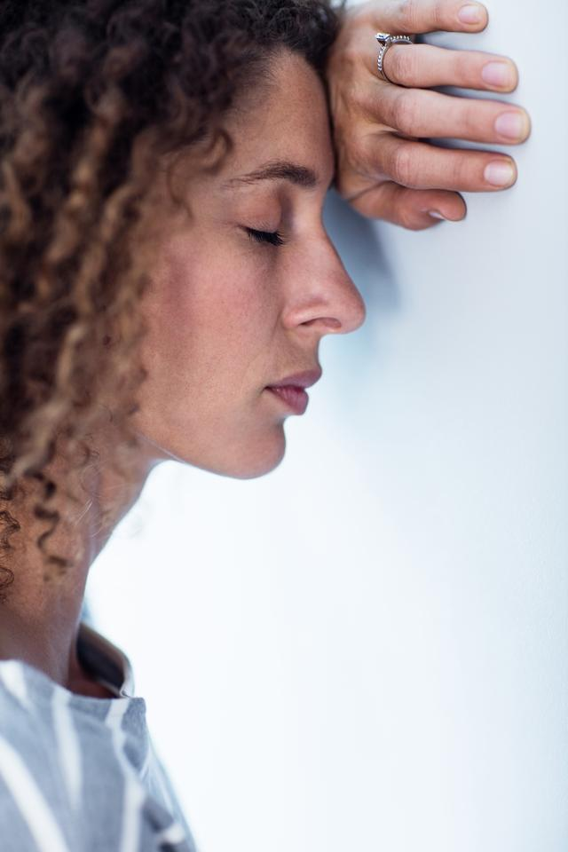 """""""Upset woman leaning on wall"""" stock image"""