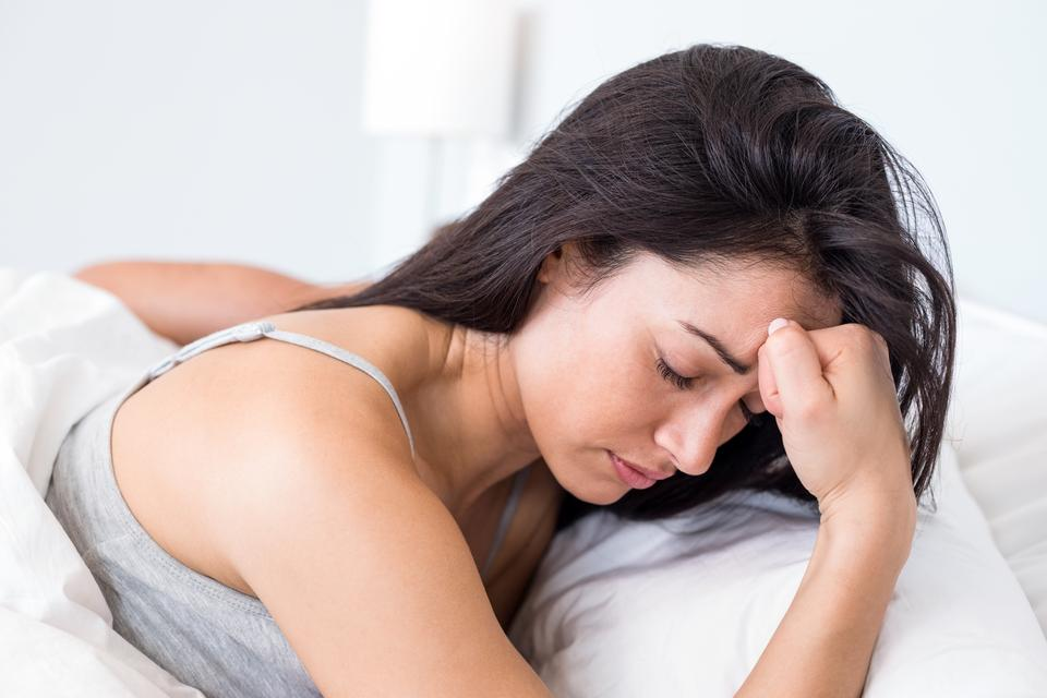 """Upset woman lying on bed"" stock image"