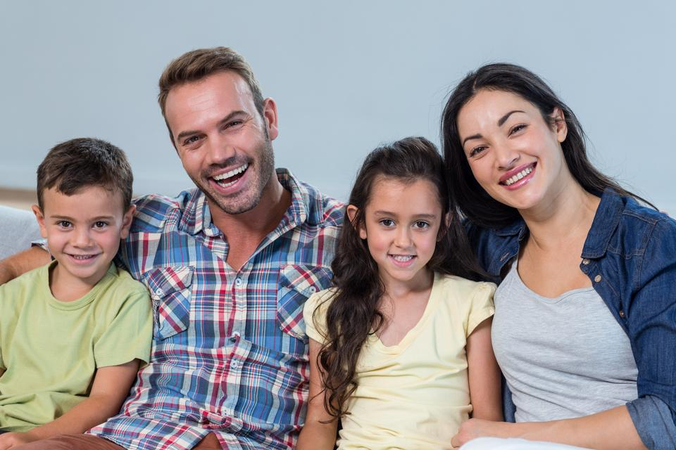 """""""Family sitting on sofa and smiling"""" stock image"""
