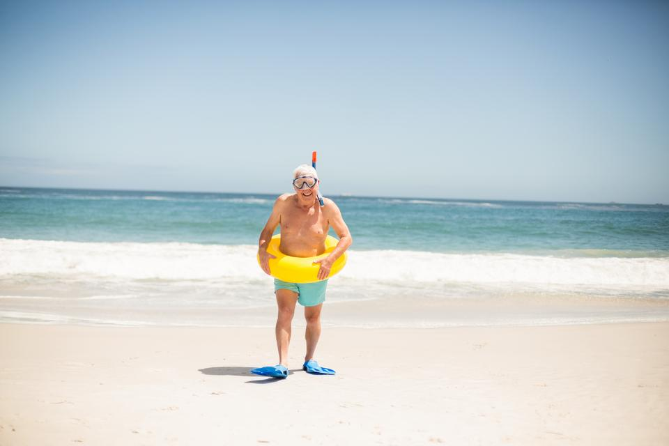 """""""Senior man with swimming ring and flippers at the beach"""" stock image"""