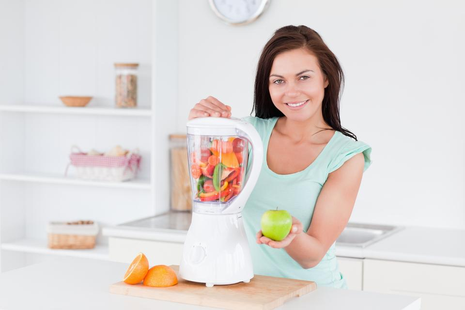 """Happy woman with a blender and an apple"" stock image"