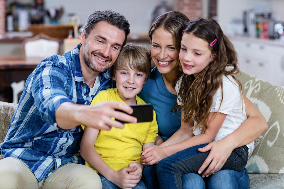 """""""Happy family taking a selfie on mobile phone"""" stock image"""