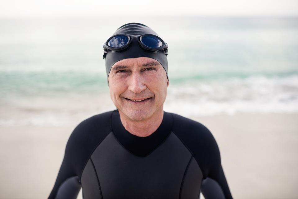 """""""Senior man in wetsuit and swimming goggles standing on beach"""" stock image"""