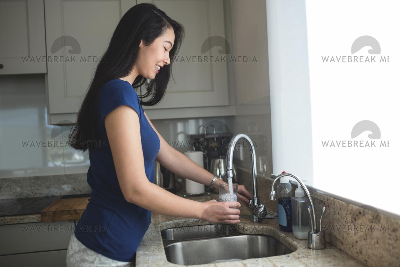 Young Woman Washing A Glass In Kitchen Sink License Download Or Print For 12 40 Photos Picfair