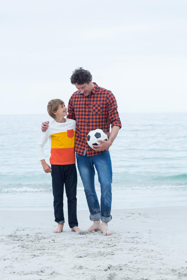 """Father and son with soccer ball at sea shore"" stock image"