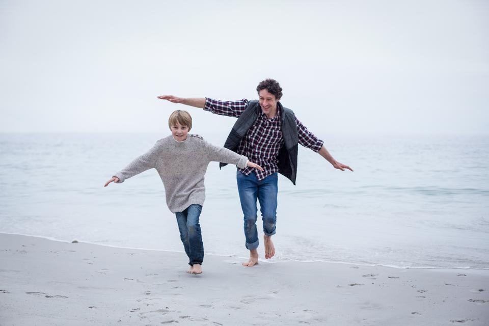 """Father and son running on beach with arms outstretched"" stock image"