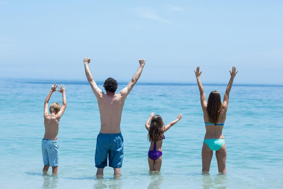 """""""Family standing with arms raised in shallow water"""" stock image"""