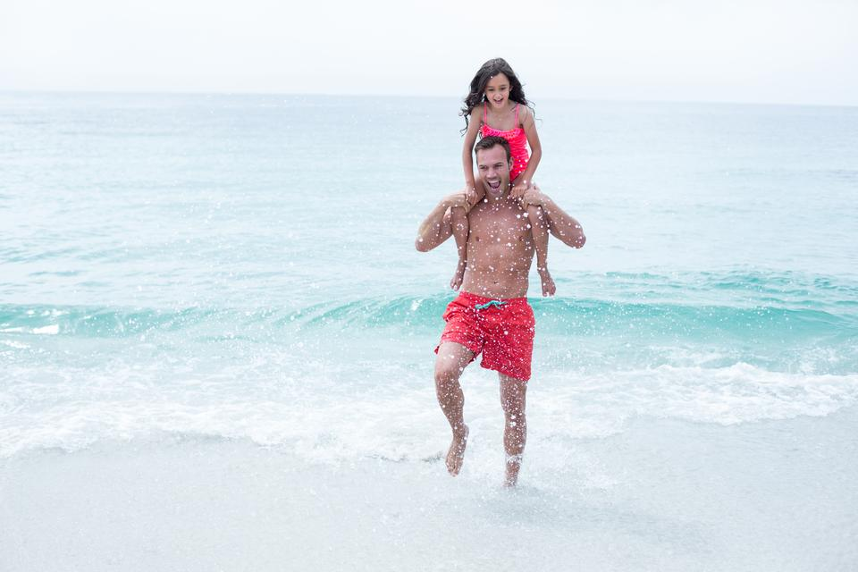 """Father enjoying while carrying daughter at beach"" stock image"