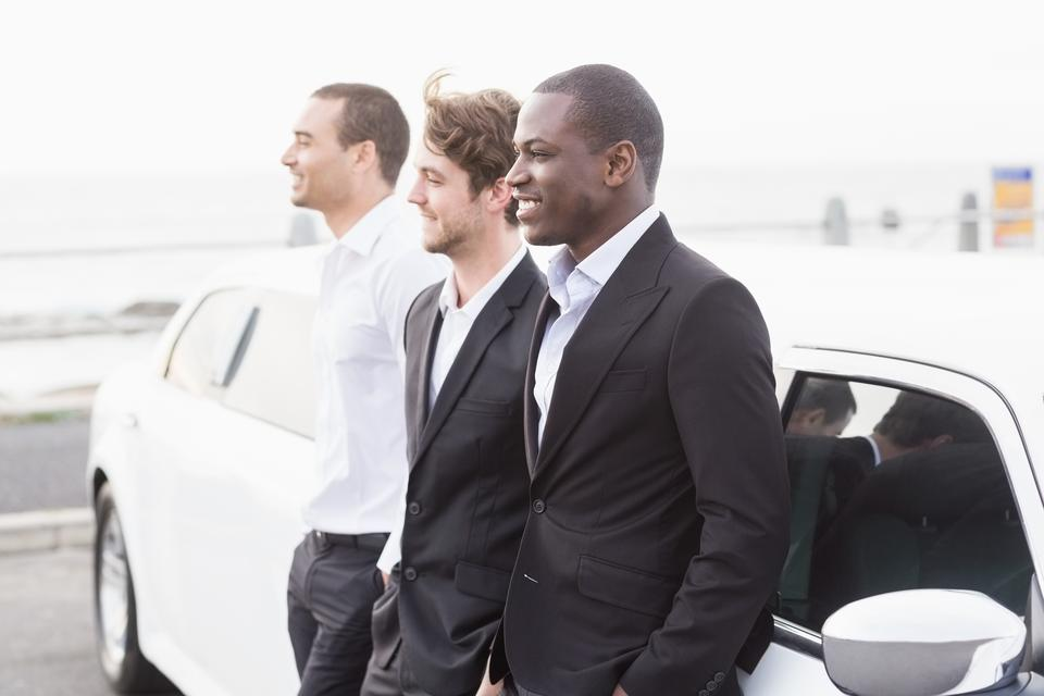 """Well dressed men posing leaning on a limousine"" stock image"