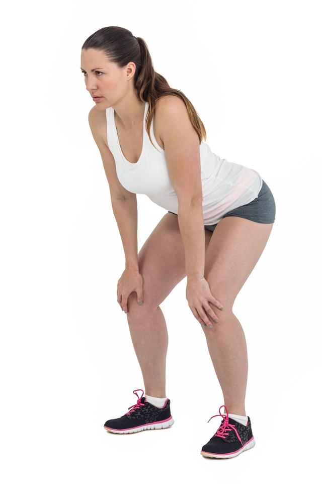 """""""Tired athlete standing with hand on knee"""" stock image"""