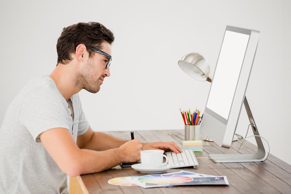 """""""Young man using pen tablet and computer"""" stock image"""