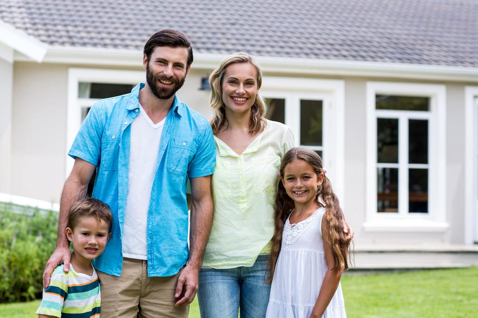 """""""Parents with children standing outside house in yard"""" stock image"""