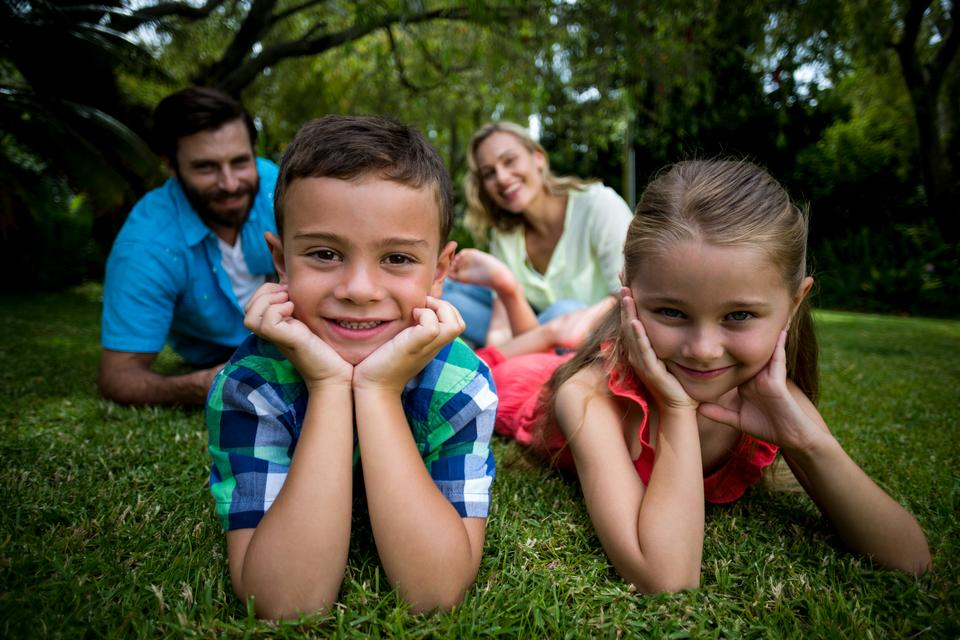 """""""Children lying with head in hands against parents in yard"""" stock image"""