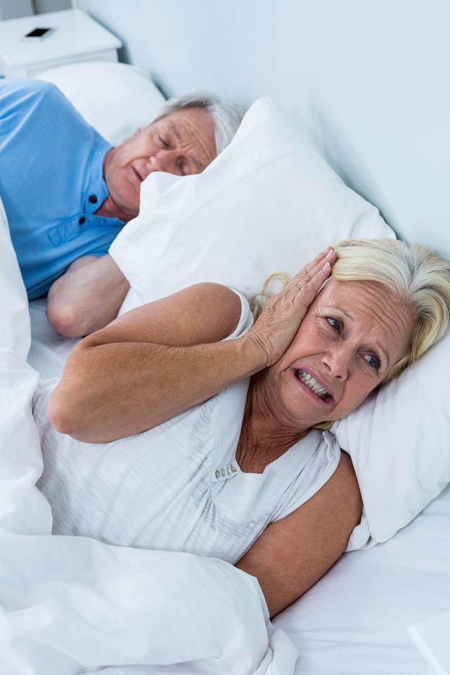 """Senior woman covering ears while man snoring"" stock image"