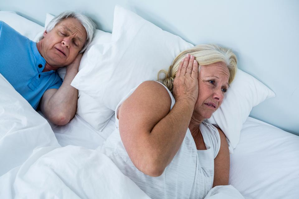 """Senior woman blocking ears while man snoring"" stock image"
