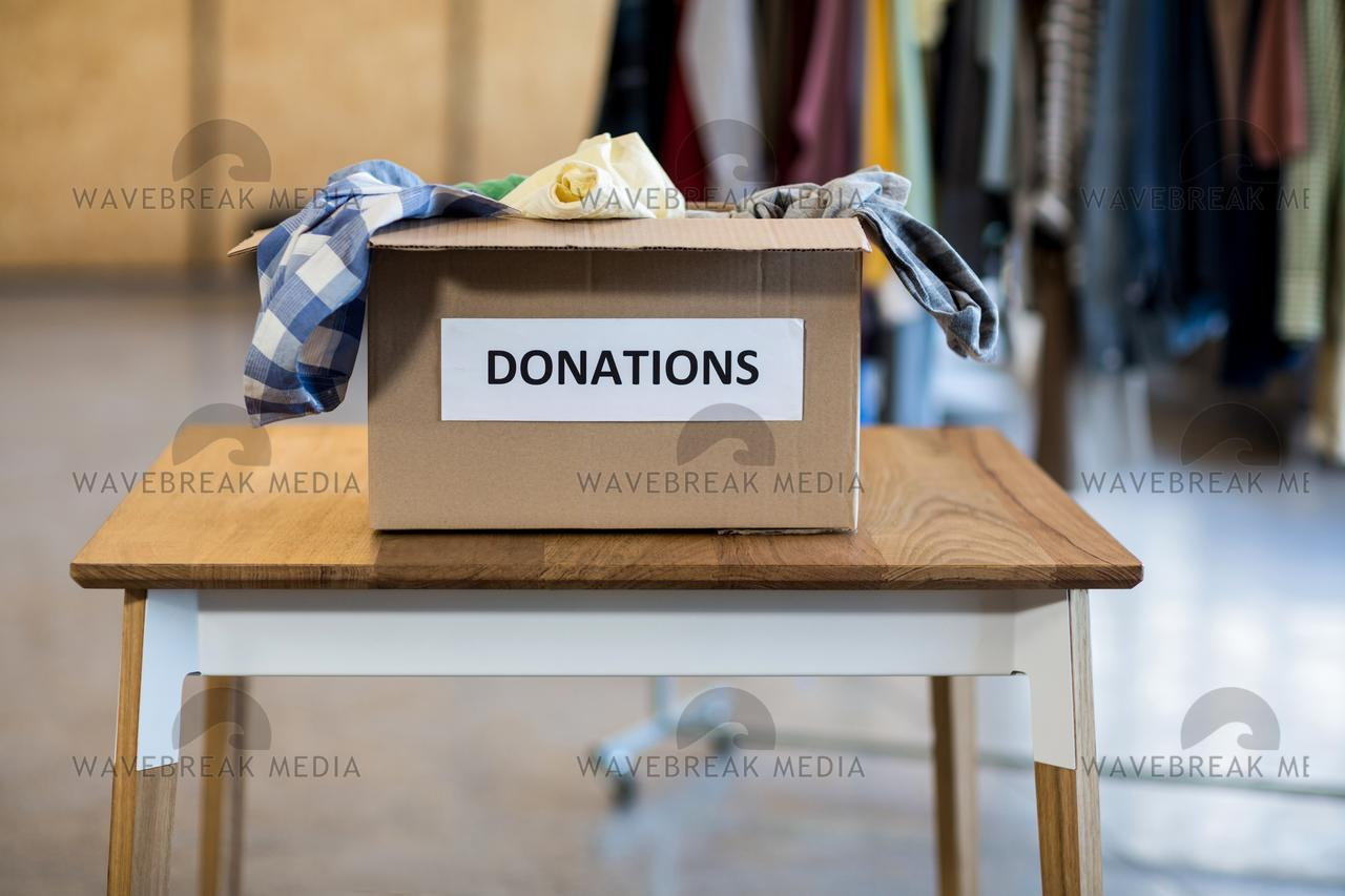 Donation box on a wooden table - License, download or print