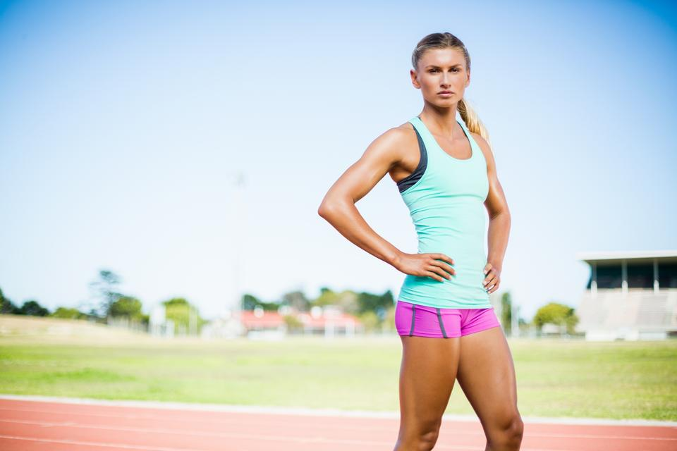 """Confident female athlete standing with hand on hip"" stock image"