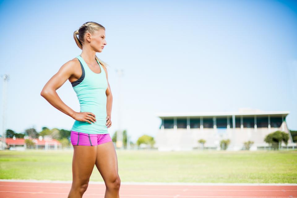 """Female athlete standing with hand on hip"" stock image"