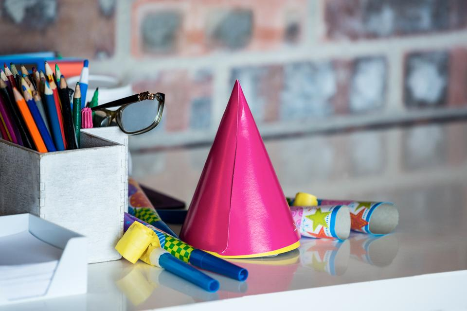 """""""Party horn, birthday hat, pen holder and spectacle on desk"""" stock image"""