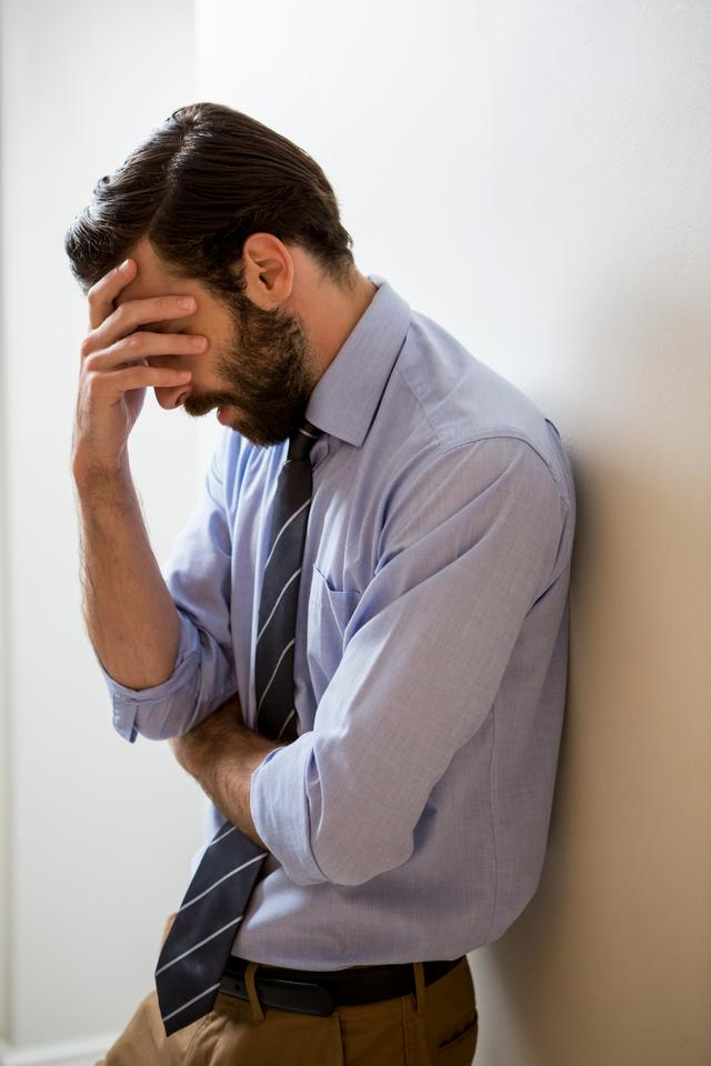 """Depressed man with hand on forehead"" stock image"