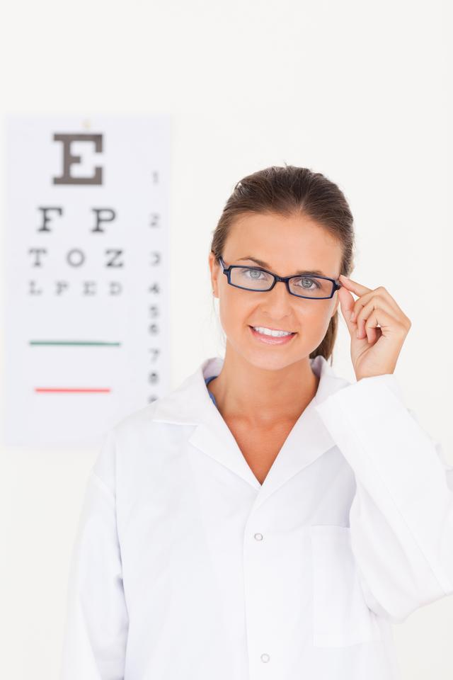 """Eye specialist wearing glasses looking into the camera"" stock image"