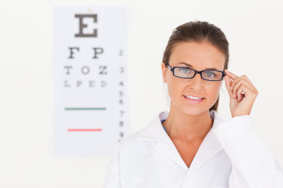"""Brunette eye specialist wearing glasses looking into the camera"" stock image"