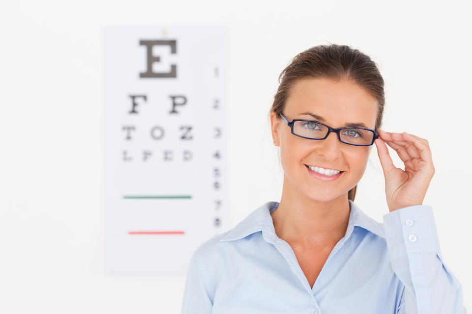 """Good looking eye specialist wearing glasses looking into the camera"" stock image"