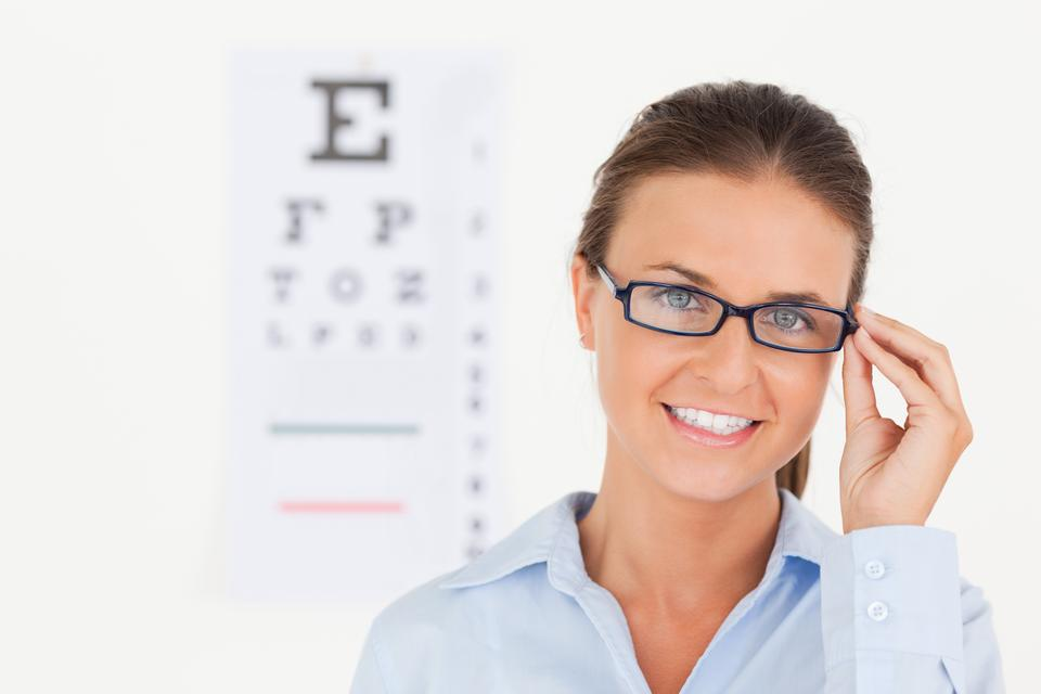 """Close up of abrunette eye specialist wearing glasses looking into the camera"" stock image"