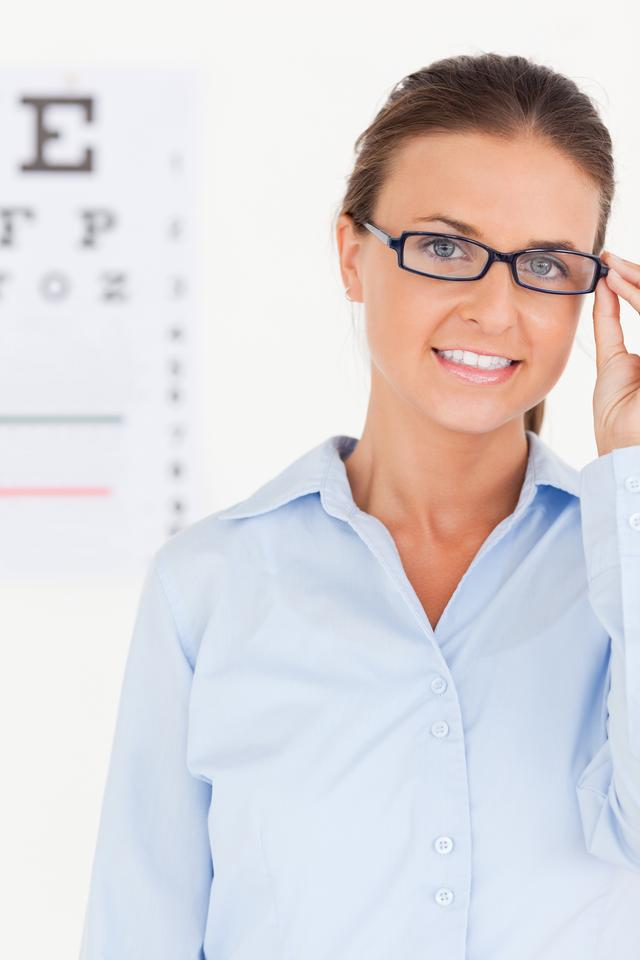 """Portrait of a brunette eye specialist wearing glasses looking into the camera"" stock image"