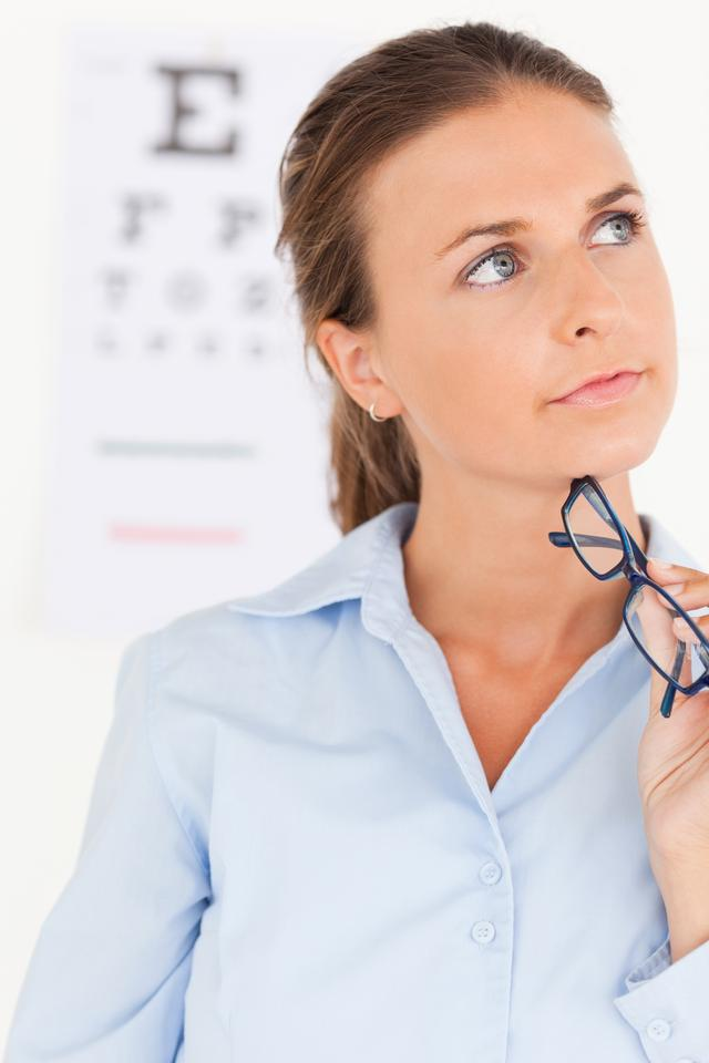 """close up of a thinking eye specialist holding glasses"" stock image"