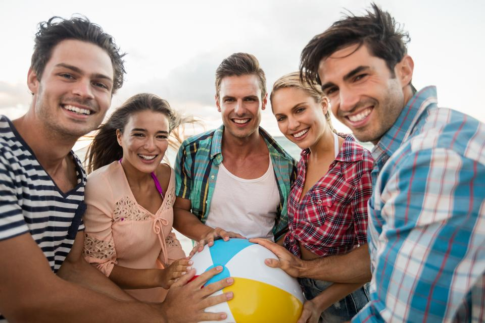 """Friends holding a beachball"" stock image"