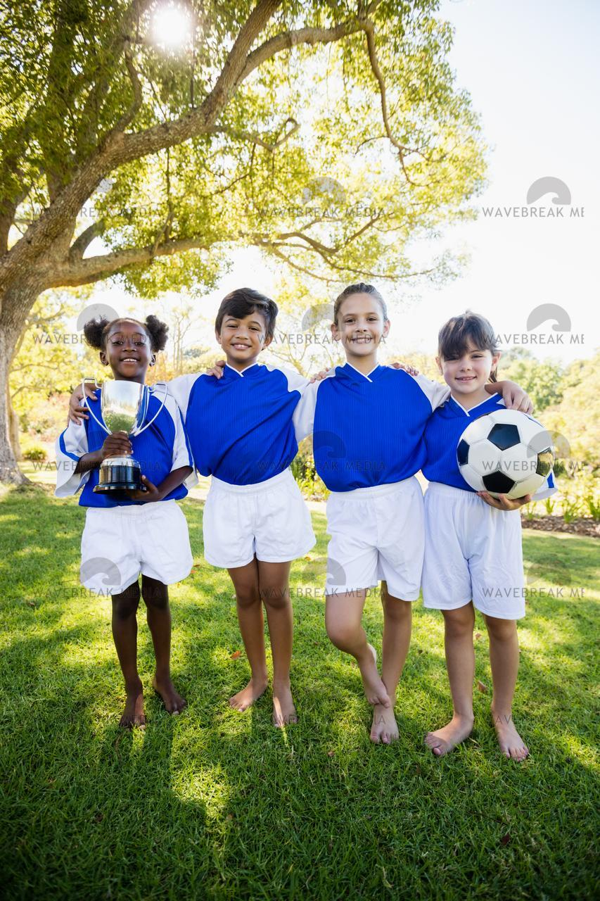 Portrait of children soccer team in raw smiling - License