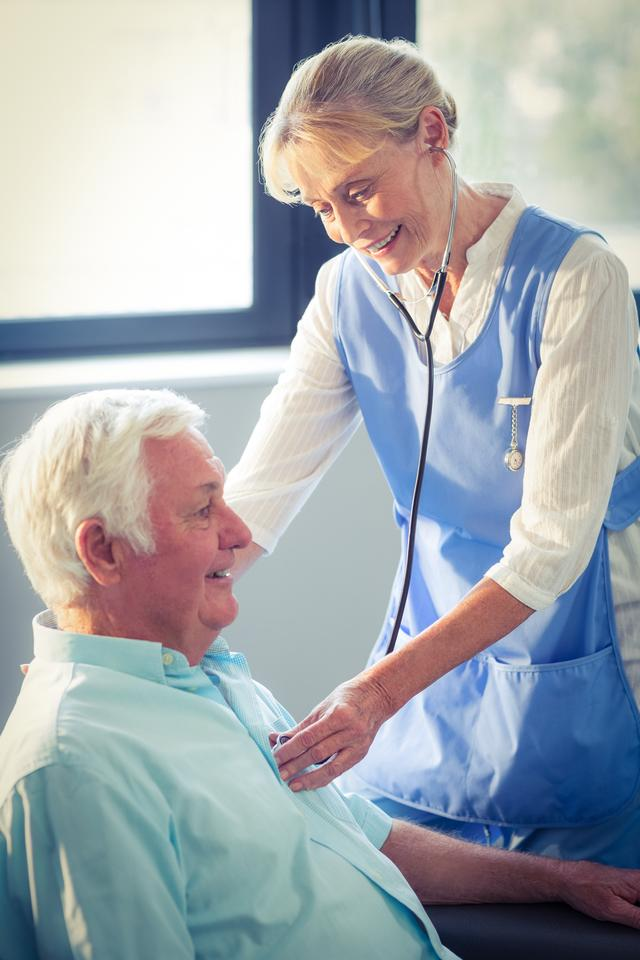 """Female doctor checking heartbeat of senior man"" stock image"