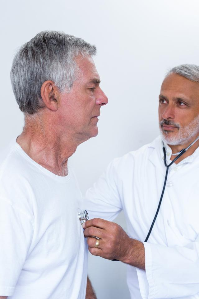 """Male doctor checking heartbeat of senior man"" stock image"