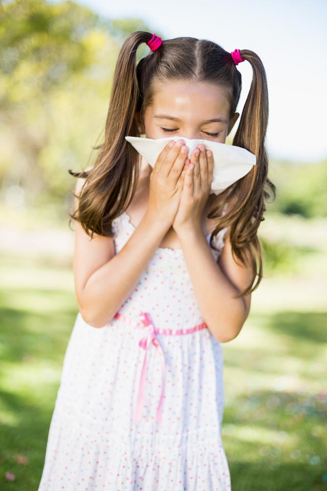 """""""Girl blowing her nose with handkerchief while sneezing"""" stock image"""