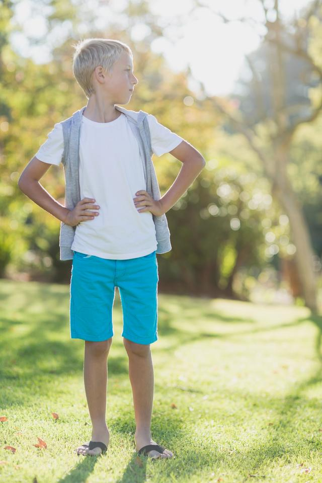 """Boy standing with hand on hip in park"" stock image"