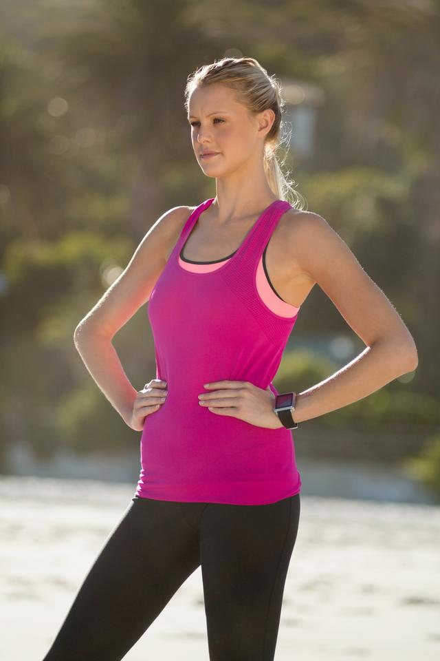 """Woman in sportswear standing on beach"" stock image"