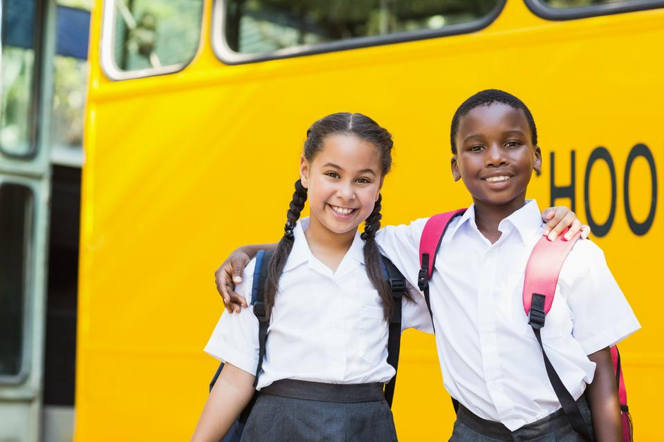 """""""Smiling kids standing in front of school bus"""" stock image"""