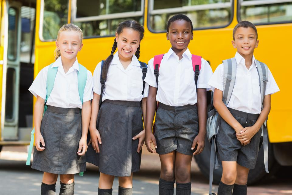 """""""Smiling kids standing together in front of school bus"""" stock image"""