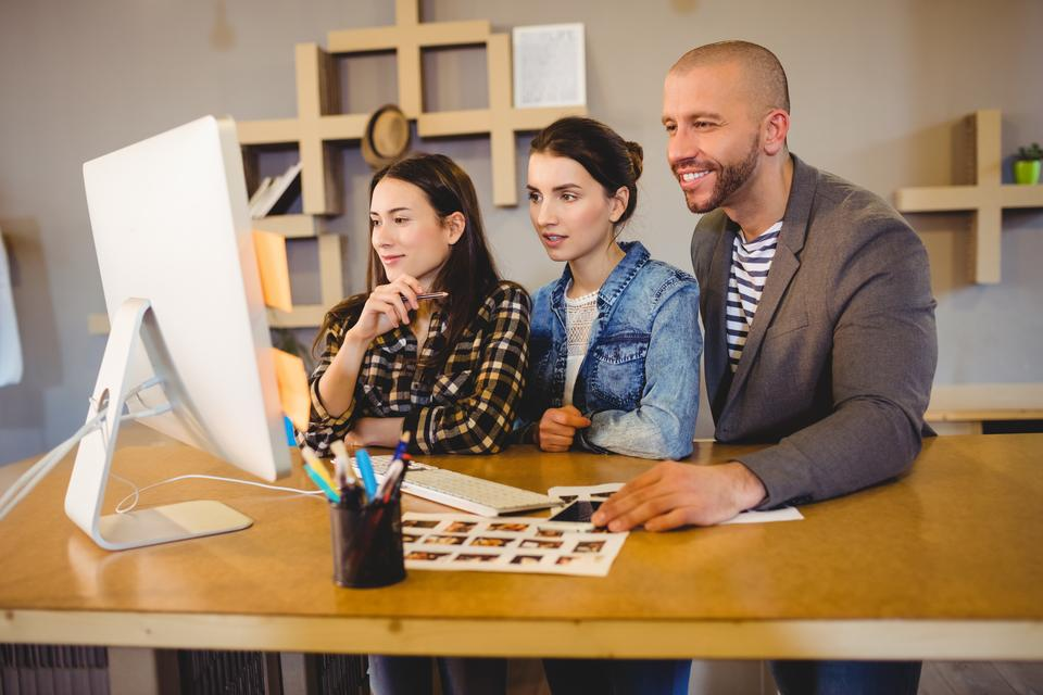 """""""Team of graphic designer working on computer"""" stock image"""