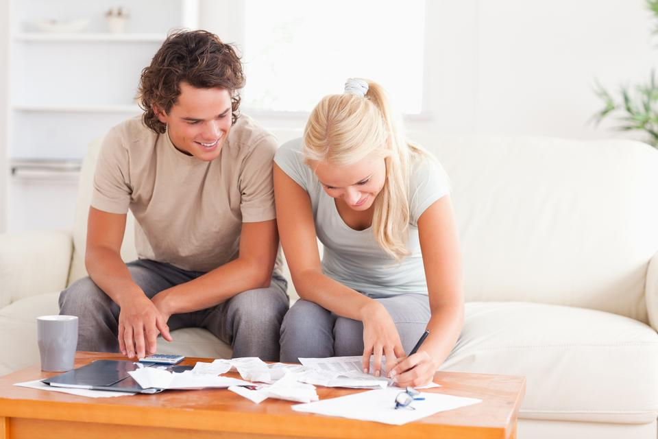 """""""Smiling couple calculating their expenses"""" stock image"""
